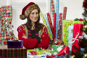 Woman wrapping Christmas presents, looking satisfied.