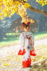 Little girl in traditional Japanese kimono with umbrella in hand