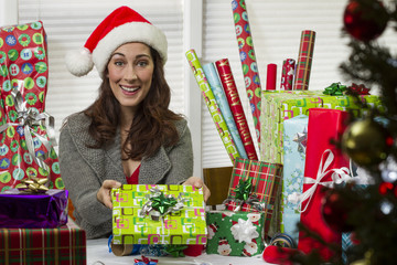 Woman wrapping Christmas presents, looking happy.