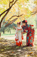 Mother and small daughter in kimono walk in autumn Park