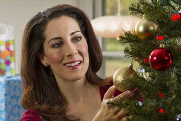 Woman decorating Christmas tree.