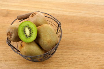 Juicy kiwi in basket on wooden table
