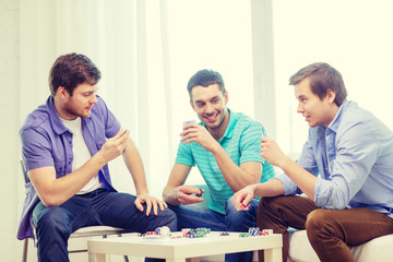 happy three male friends playing poker at home