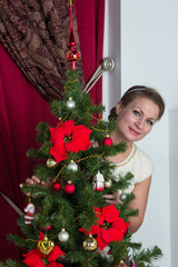 Woman decorate Christmas tree at home