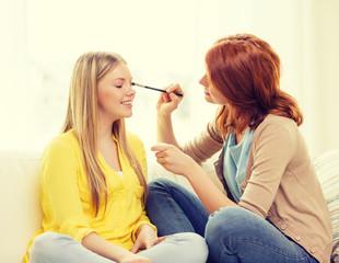 two smiling teenage girls applying make up at home