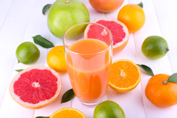 Juice and many citrus on table close-up