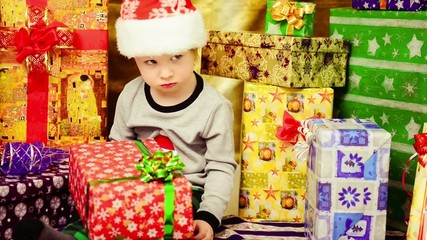 boy upset with holiday present sitting inside colorful boxes