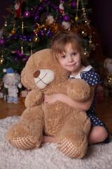 nice girl with a big bear at a fir-tree