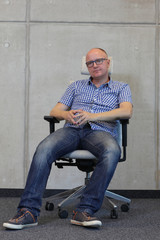 middle age balding man bad sitting position on chair