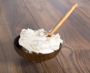 thick sour cream in a bowl and wooden spoon
