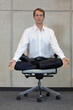 canvas print picture - meditating caucasian businessman in lotus pose on office chair