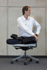 businessman in lotus pose on office chair practicing yoga