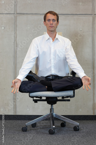 canvas print picture meditating caucasian businessman in lotus pose on office chair
