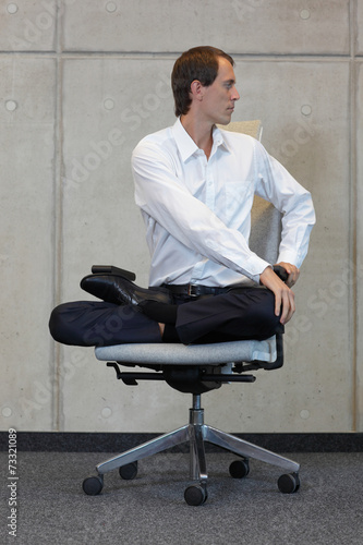 canvas print picture businessman in lotus pose on office chair practicing yoga