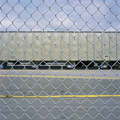 Train car through a chain link fence