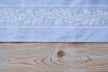licht blauw tafellaken met borduursel op houten tafel