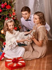 Family with children  dressing Christmas tree.