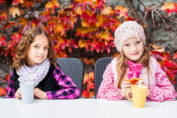 Adorable little girls drinking hot chocolate on a terrace