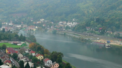 Timelapse of small village life, cars trains, wind on river