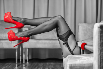 Legs with stockings, garter belt and red high heels shoes