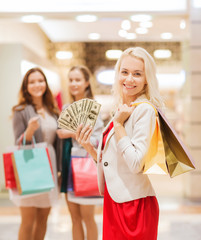 young women with shopping bags and money in mall