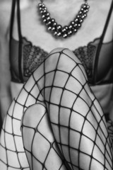 close up of female legs in fishnet stockings and high heels
