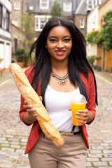 woman holding a baguette and fresh fruit juice