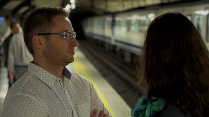Couple waiting for subway and talking on platform, steadycam sho