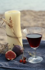 Candle and red wine on the beach