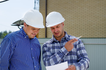 Two builders or engineers discussing paperwork