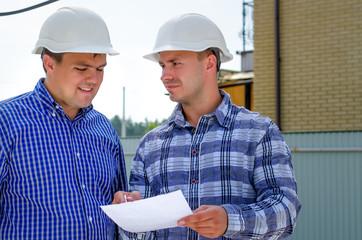 Two builders or engineers discussing paperwork
