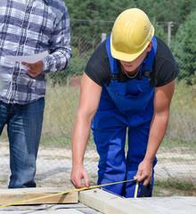 Builder measuring a wooden beam