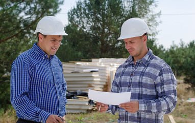 Two engineers having a discussion on site