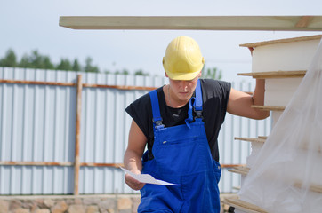 Worried builder on site with a document
