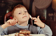 Contented little boy eating cake for dessert