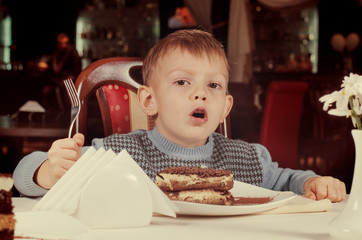 Cute little boy about to tuck into a slice of cake