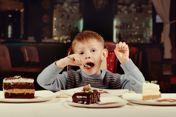 Little boy eating a slice of cake with gusto