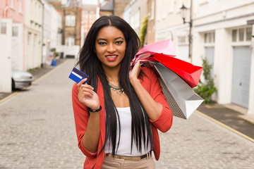 young woman with shopping bags holding a credit card.