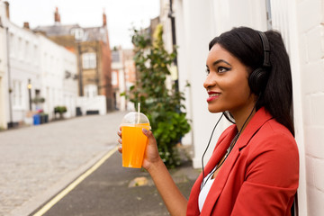 a young woman holding a smoothie and listening to music.