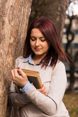 Young woman standing in park with book