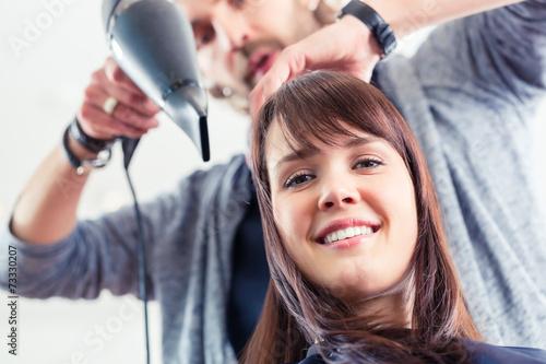 canvas print picture Friseur föhnt Frau die Haare im Friseursalon