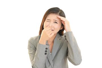 鼻をおさえる女性