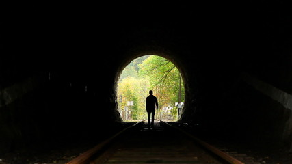 Man walking in the tunnel, dark silhouette, searching way out