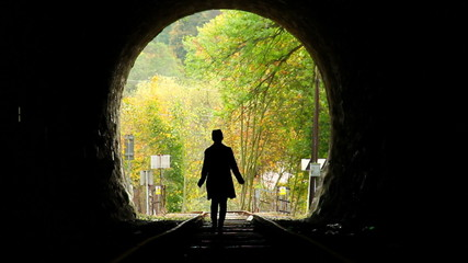 Woman in tunnel walks strayed cautiously railroad way out dark