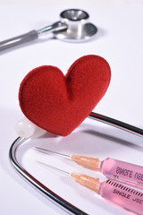 Red heart on stethoscope and syringe