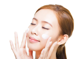 beautiful young woman applying cosmetic cream  on her face
