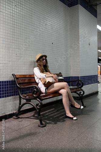 Dziewczyna na ławce w stacji metra