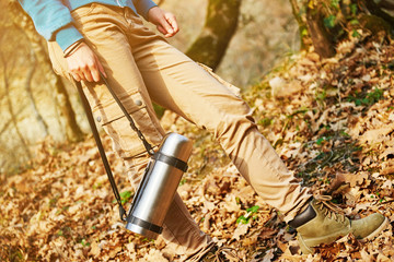Unrecognizable hiker holding thermos