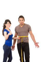 beautiful girl holding measuing tape around handsome muscular