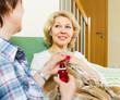 retirement home employee offering  mixture to  patient